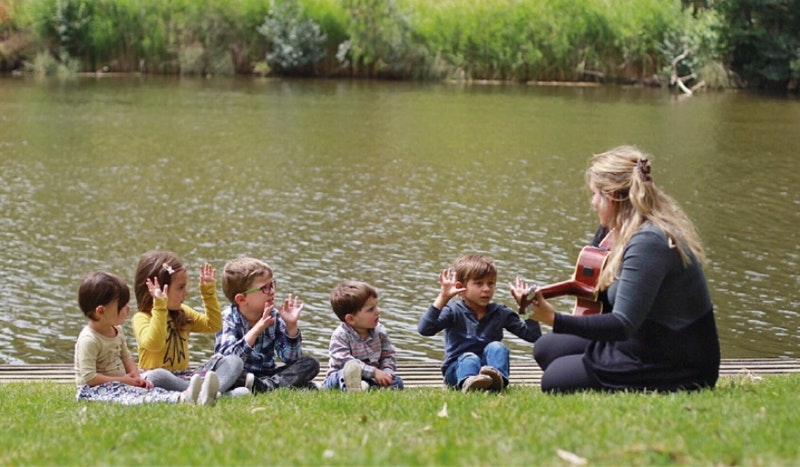 on a pond's bank a girl is playing guitar to children