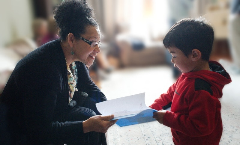 young boy shows his drawing to a teacher
